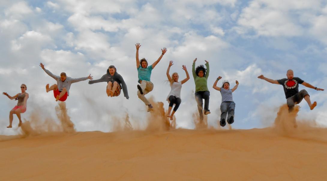 Åtta volontärer hoppar ner i en sanddyn under deras volontärresa utomlands med Projects Abroad.